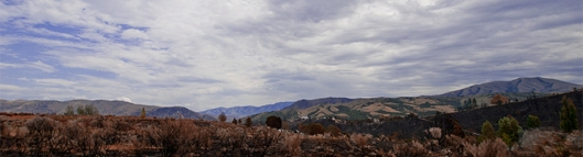 scene of clouds, monntains overlooking burned area.