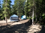 Kitchen and sleeping tents on wooded campsite