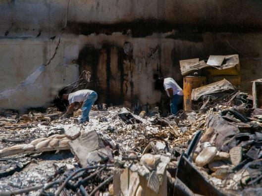 men wading through debirs from the burn