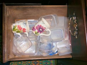 Mugs in a drawer mong the leftover containers