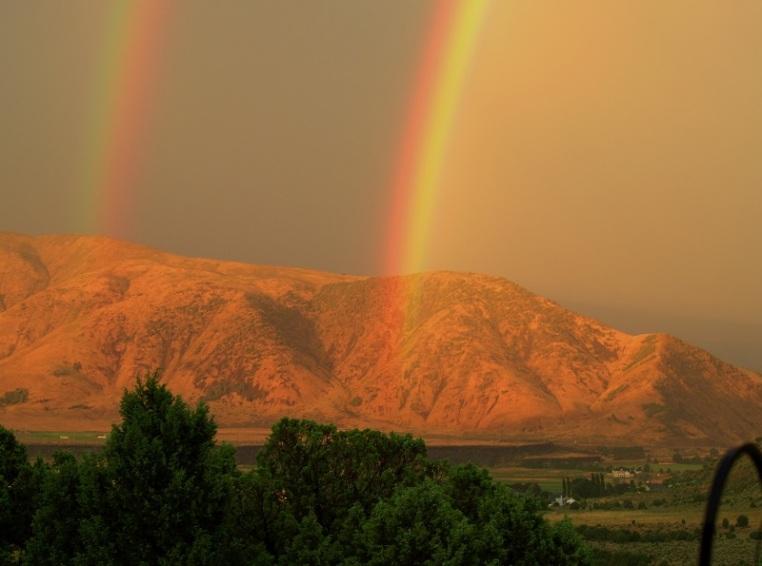rainbow across mountain dust and smoke