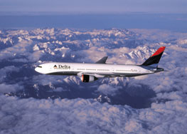 delta jet flying over snow covered mountains with blue sky and clouds