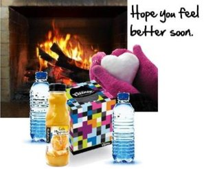 tissues, bottles of juice and water, fireplace, gloved hands holding snow heart and feel better soon texbox of t