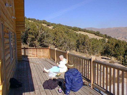 male and female sitting on floor of deck eating picnic with mountaints in the background