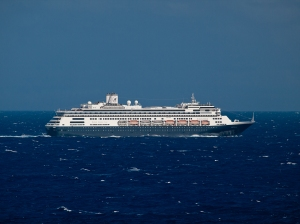 cruise ship with navy colored bottom half sailing on water that is navy colored with light chop