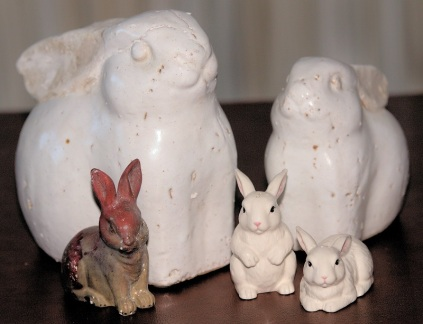 five mixed sizes of ceramic bunnies ranging from 2 1/2 to 12 inches high. One is brown with read burned into it