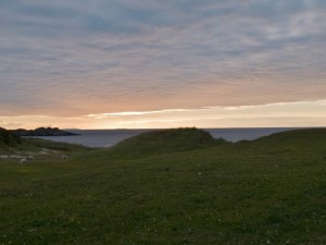 green hill leading to beach with sunrise over small bay