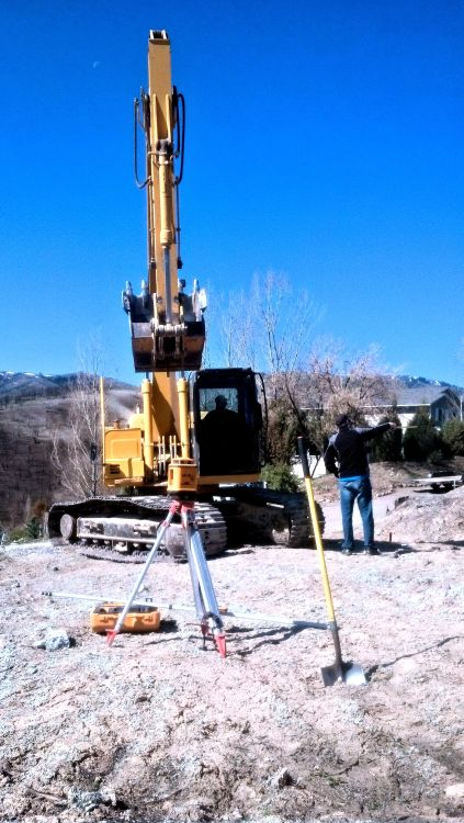earthmoving equipment poised, man pointing to location of work area