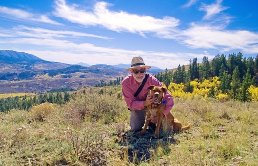 man and dog posing at the top of a mountain trail with sagebrush and grass and a very blue sky.