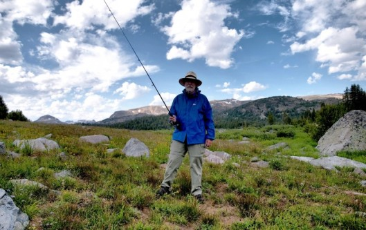 man with fishing pole posed against rocky mountains