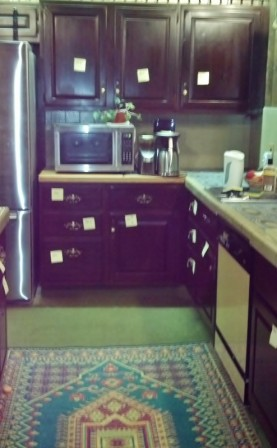 picture looking at kitchen cabinets with multiple yellow post-its hanging on the cabinets and drawers
