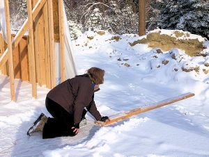 House being framed, woman in snow on floor holding out a 2 by 4