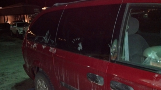 red van in dark parking lot with white handprints on it.