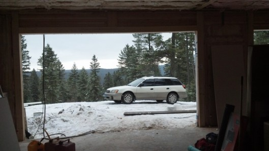 looking out a garage under construction with white subaru in snow with mountains behind