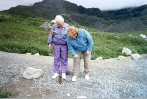two mature women standing on a path in front of rugged mountains looking at a marmot sitting at their feet.