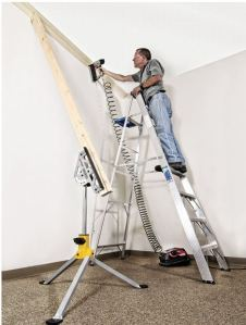 Man standing on ladder nailing ceiling molding with Jawstand holding 2 x 4s that brace the unfastened end of the molding