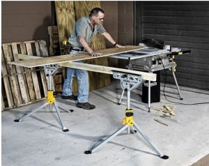 man cutting plywood on a table saw using two Rockwell Jawstands with a 2 x 4 between them to balance the other end of the plywood.