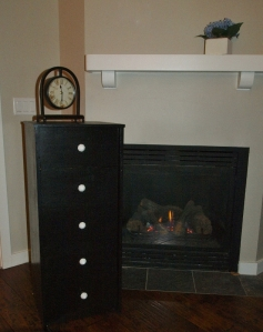 black chest of drawers by fireplace, clock on chest, flowers on fireplace mantel