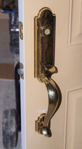 georgean style brass entry door handle set with small portion of door it is mounted on showing
