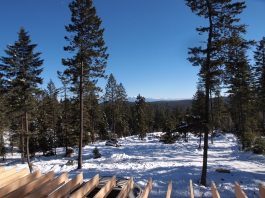 View overlooking house under construction floor joists across snow and evergreen trees to distant mountains.