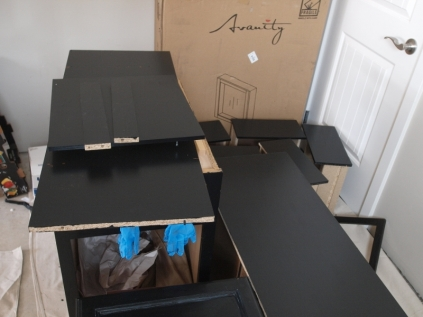 stack of furniture parts painted black with blue latex gloves hanging from the middle