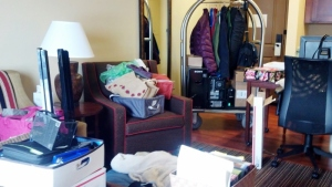 hotel room showing boxes, clothes and computers in need of packing