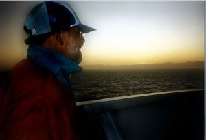 man looking at sunset over bow of boat