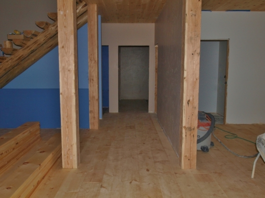 room scene with 8x8 hand hewn posts, log stairs and wide board pine flooring