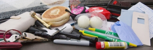 photo of things taken from a woman's purse including white and pink wallet, lipstick, dog poop bag, building supplies and pens