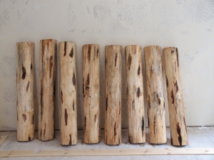 eight half logs that will become stair treads lined up against a dry wall that has been textured but not painted in new construction