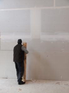 """Man holding half of a 48"""" log that will become a stair silhouetted against blank dry wall that has been taped but not textured"""