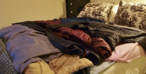 bed covered with coats and vests and a curtain to use for covers