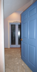 dark blue door opening on to paint splattered floor under construction leading to light blue glass french doors