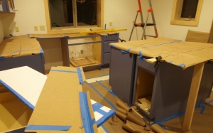 kitchen under construction showing counters covered by brown craft paper with tile designs hand drawn on paper. Room is messy with scraps of paper and tile templates. Ladder shows in back