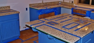 kitchen under construction with blue painter tape all over counter tops in geometric shapes