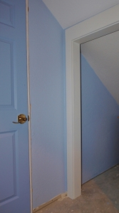 sloped wall bisected by door frame. The ceiling is sloped and white, the wall blue. The door frame bisects.