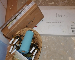 house construction, one laundry basket with brass candle lamps and shop towels in it, one rectangular brown cardboard box and a white cardboard box marked HOME