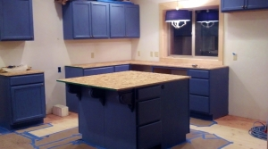 kitchen under construction with cabinets in place, no appliances or sink