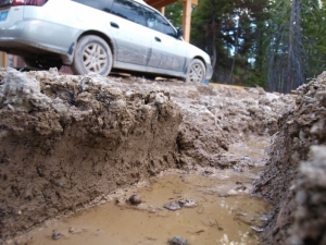 deep muddy rut beside a subaru car