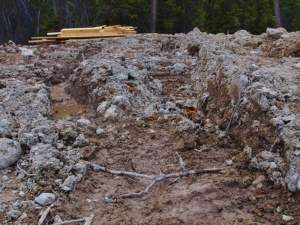 ground level shot of muddy ruts with pile of 2 x 6 wood stacked at far end of the ruts