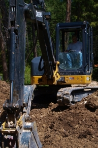 small excavator with bucket in front digging dirt