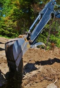 the bucket of an excavating equipment shown emptying dirt