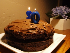 chocolate cake with two candles facing opposite directions. The number facing front is a 0 and the back of the number on the other side of the cake is a 2.