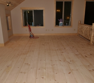 looking across room at newly sanded, unfinished pine floor boards with sanding machine at the far left end of the room.