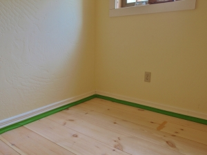 the corner of a room with green masking tape on the floorboards