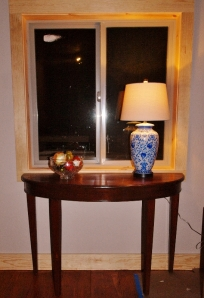 half-round table sitting in front of window with blue china lamp and bowl of fruit on it