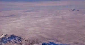 airel view of Mt Hood and Mt St Helens showing just their peaks above a blanket of clowds