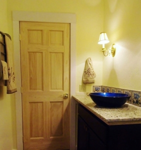 bathroom counter with blue and yellow tile back splash, white pine door, colonial wall light, countertop with blue vessel sink